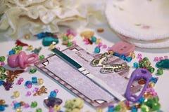 La prueba de embarazo positiva en marco del libro del pedazo con la mariposa, los accesorios lindos del bebé y la semilla colorea Imagen de archivo libre de regalías
