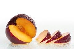 La prugna fresca fruttifica con le fette e le gocce dell'acqua. Fotografia Stock Libera da Diritti