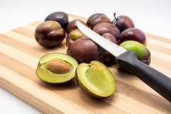La prune juteuse cuted dans la moitié sur le conseil en bois photo libre de droits