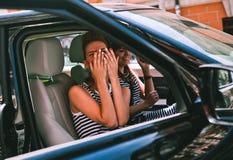 La puerta abierta del coche de la muchacha cubrió sorpresa de las manos de la cara imagenes de archivo