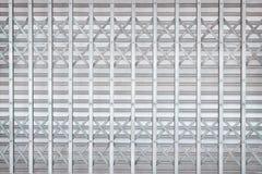 La puerta de acero rodante gris o de plata o la puerta del obturador del rodillo adentro entrelaza los modelos para el fondo imagen de archivo libre de regalías