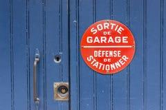 La puerta de madera azul sin el estacionamiento canta en francés Foto de archivo