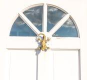 La puerta de madera blanca a contener con un golpeador de cobre amarillo formó como un li Foto de archivo libre de regalías