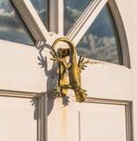 La puerta de madera blanca a contener con un golpeador de cobre amarillo formó como un li Imagenes de archivo