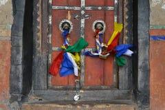 La puerta de madera de Borgoña con el tibetano coloreó las cintas en los anillos, cintas que agitaban, la entrada al templo budis Imagenes de archivo