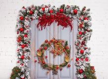 La puerta de madera de la Navidad con el abeto ramifica una decoración del Año Nuevo Fotografía de archivo