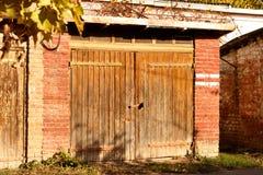La puerta de madera en el granero del ladrillo rojo Imágenes de archivo libres de regalías
