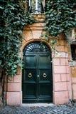 La puerta de madera de la entrada cubierta con la hiedra verde Ventanas viejas hermosas en Roma (Italia) Fotos de archivo libres de regalías