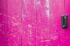 La puerta de madera vieja rosada marcó con una cicatriz con la manija negra Imagenes de archivo
