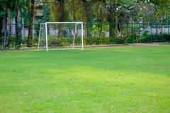 La puerta del fútbol y los pequeños céspedes verdes al ensayo juegan Imagenes de archivo