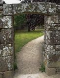 La puerta en la pared de piedra antigua del jardín Fotos de archivo libres de regalías