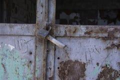 La puerta oxidada vieja sujeta por vieja textura del candado imagenes de archivo