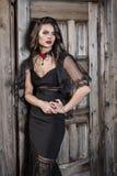La puerta vieja es una muchacha en un vestido negro Foto de archivo libre de regalías