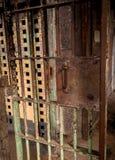 La puerta vieja pintada y aherrumbrada de la prisión lleva a un pasillo Fotografía de archivo