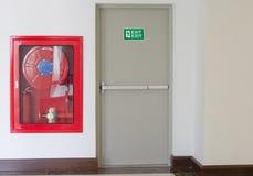 La puerta y el fuego de la salida de socorro extinguen el equipo Imagen de archivo