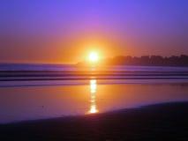 La puesta del sol épica refleja en el océano y la playa en un cielo claro vacío DA Foto de archivo