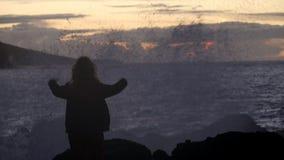 La puesta del sol, agita, salpica y la muchacha disfruta de la belleza de la naturaleza almacen de video