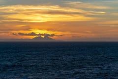 La puesta del sol anaranjada de los cielos detrás de las montañas en Marruecos vio del Estrecho de Gibraltar foto de archivo