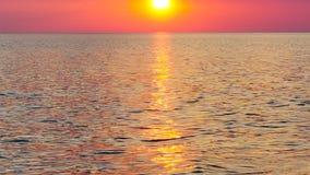 La puesta del sol anaranjada reflej? en las peque?as ondas Las ondas brillantes en la puesta del sol imagenes de archivo