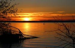 La puesta del sol anaranjada se refleja en el agua del lago foto de archivo