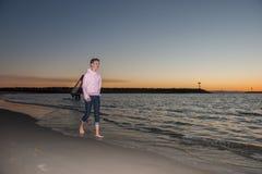 La puesta del sol camina a lo largo de la playa Imagen de archivo libre de regalías