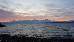La puesta del sol colorida majestuosa sobre el fiordo y el pico de montaña nevoso ajardinan metrajes