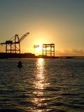 La puesta del sol con el levantamiento cranes en los terminales del cargo del envase Fotos de archivo libres de regalías