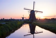 La puesta del sol con los molinoes de viento holandeses tradicionales reflejó en el wa tranquilo Foto de archivo libre de regalías