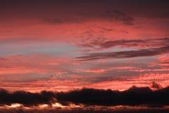 La puesta del sol con un cielo azul, rosado y anaranjado Fotografía de archivo