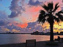 La puesta del sol de la ciudad de Pafos, terraplén, nubes, envía Chipre Imagenes de archivo