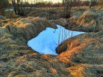 La puesta del sol de la primavera, en campo es nieve pasada Fotos de archivo libres de regalías