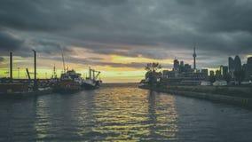 La puesta del sol de oro de la oscuridad de Toronto atraca tirones del puerto Fotografía de archivo libre de regalías