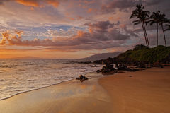 La puesta del sol de oro de Maui y trata ondas con suavidad Foto de archivo