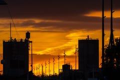 La puesta del sol de oro en el horizonte de la ciudad de Auckland con la silueta del centro de ciudad y el cielo de Auckland se e Fotos de archivo
