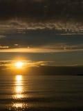 La puesta del sol de oro hermosa en el mar adriático tranquilo, haz pasado del sol hace una trayectoria de oro en superficie wave Foto de archivo libre de regalías