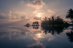 La puesta del sol de oro mágica con las nubes en una playa en Maldivas, reflejó en una piscina del infinito foto de archivo libre de regalías