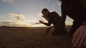 La puesta del sol de rogación de la naturaleza del hombre musulmán religioso de dos hombres siluetea la religión