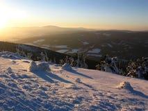 La puesta del sol del invierno en las montañas nevosas Fotografía de archivo