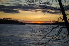 La puesta del sol del invierno sobre el hielo cubrió el lago Fotos de archivo libres de regalías