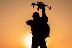 La puesta del sol del soldado se agachó en uniforme Fotos de archivo libres de regalías