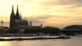 La puesta del sol detrás de la catedral de Colonia, los trenes en el puente de Hohenzollern y el carbón barge la navegación en el metrajes