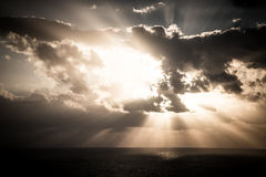La puesta del sol dramática irradia a través de un cielo oscuro nublado sobre el océano Fotografía de archivo libre de regalías