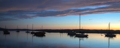 La puesta del sol en el crepúsculo sobre los barcos del puerto de la bahía de Morro y Morro oscilan en la costa central de Califo imagen de archivo
