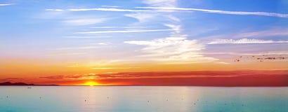 La puesta del sol en el mar con alguno envía Imágenes de archivo libres de regalías