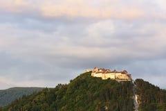 La puesta del sol en el rumano de la ciudadela de Rasnov: Cetatea Rasnov, alemán: El Burg de Rosenauer es un monumento y una seña imagenes de archivo