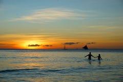 La puesta del sol en la playa con los pares que llevan a cabo las manos Foto de archivo libre de regalías