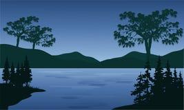 La puesta del sol en montañas acerca al lago Foto de archivo