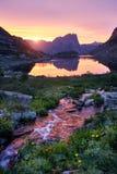 La puesta del sol en montañas acerca al río Luz del sol reflejada en los tops de la montaña La luz de oro del cielo reflejó en un fotografía de archivo libre de regalías