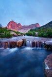 La puesta del sol en montañas acerca al río Luz del sol reflejada en los tops de la montaña La luz de oro del cielo reflejó en un imagen de archivo
