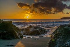 La puesta del sol en la playa de Fuerteventura con lava oscila Imagenes de archivo